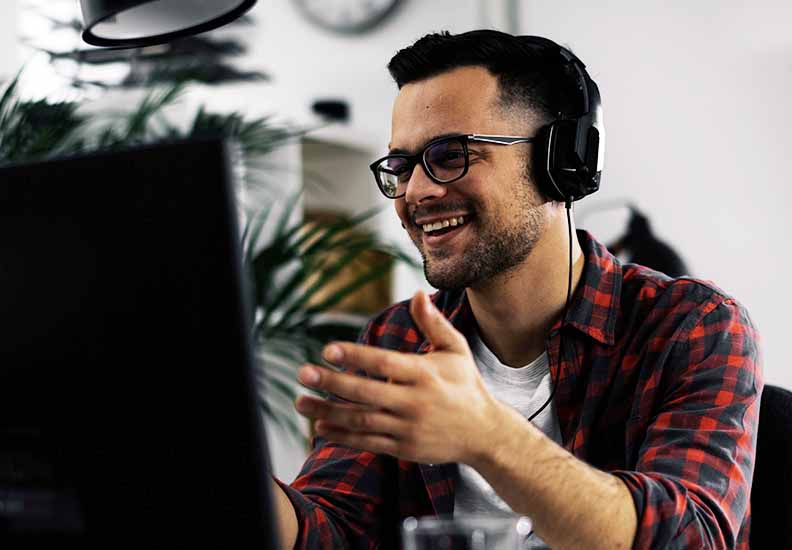 Man looking at computer with headphone