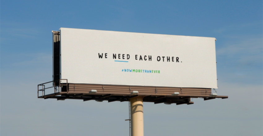 Cartelera de carretera con mensaje de Cox: Nos necesitamos unos a otros en el centro - #NowMoreThanEver