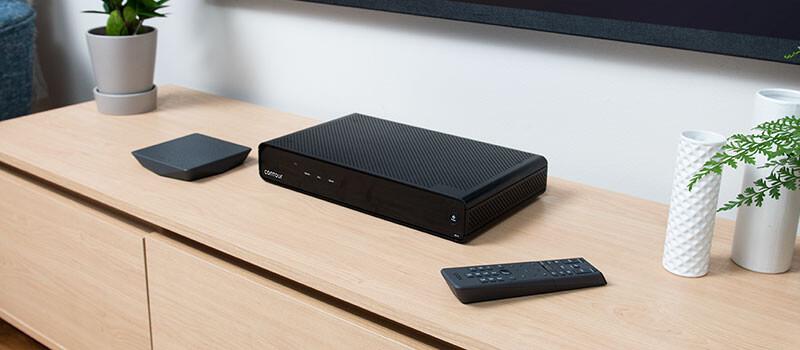 Caja del reproductor de <i>streaming</i> Cox Contour y control remoto sobre un aparador con una TV en la pared de fondo