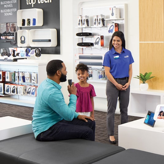 Father sitting down with daughter in store with associate