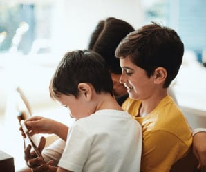 Children in group looking at tablet