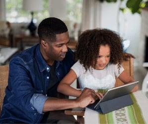 Dad teaching daughter on tablet