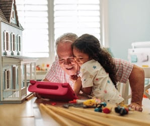 Granddad with granddaughter playing with toys