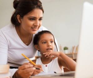 teacher behind student looking at computer