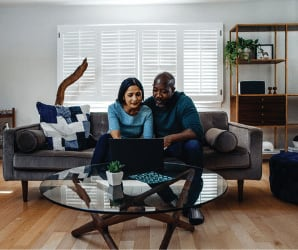 Womand and man sitting on couch using laptop