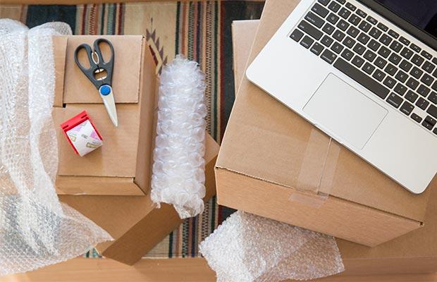Imagen: Cajas y suministros para mudanza con una laptopencima
